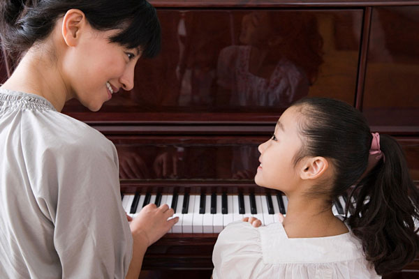 Woman teaching girl to play piano
