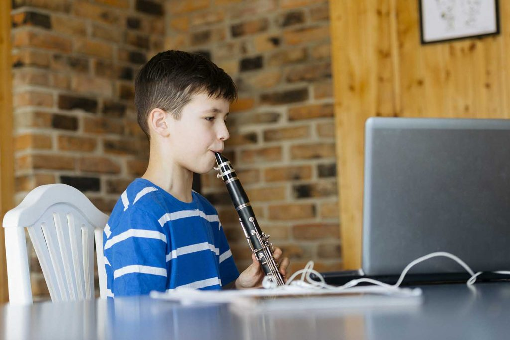 Boy with a clarinet plays music. Online music lesson concept