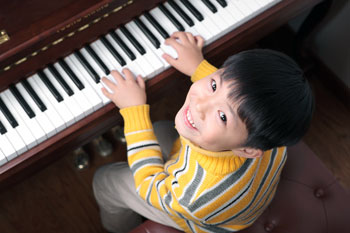 Smiling Boy Plays Piano